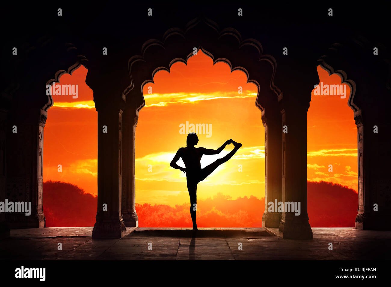 Man silhouette doing yoga advance balance asana in old temple at orange sunset sky background - Stock Image