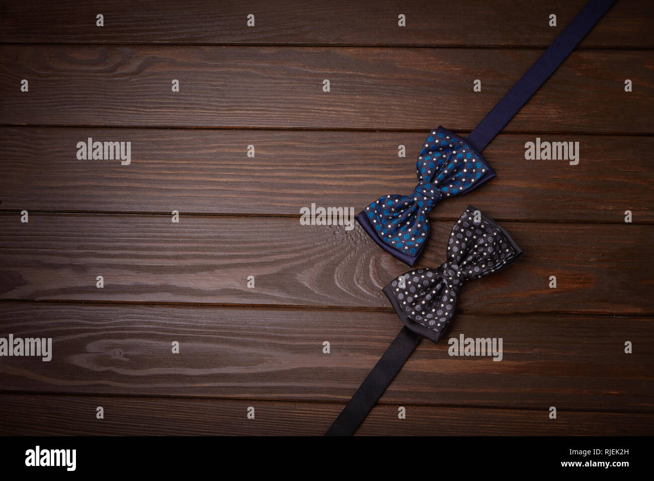 Two dark bowties with polka dots on a dark brown wooden board background. Invitation to  party place, special occasion, top view, space for text, copy - Stock Image