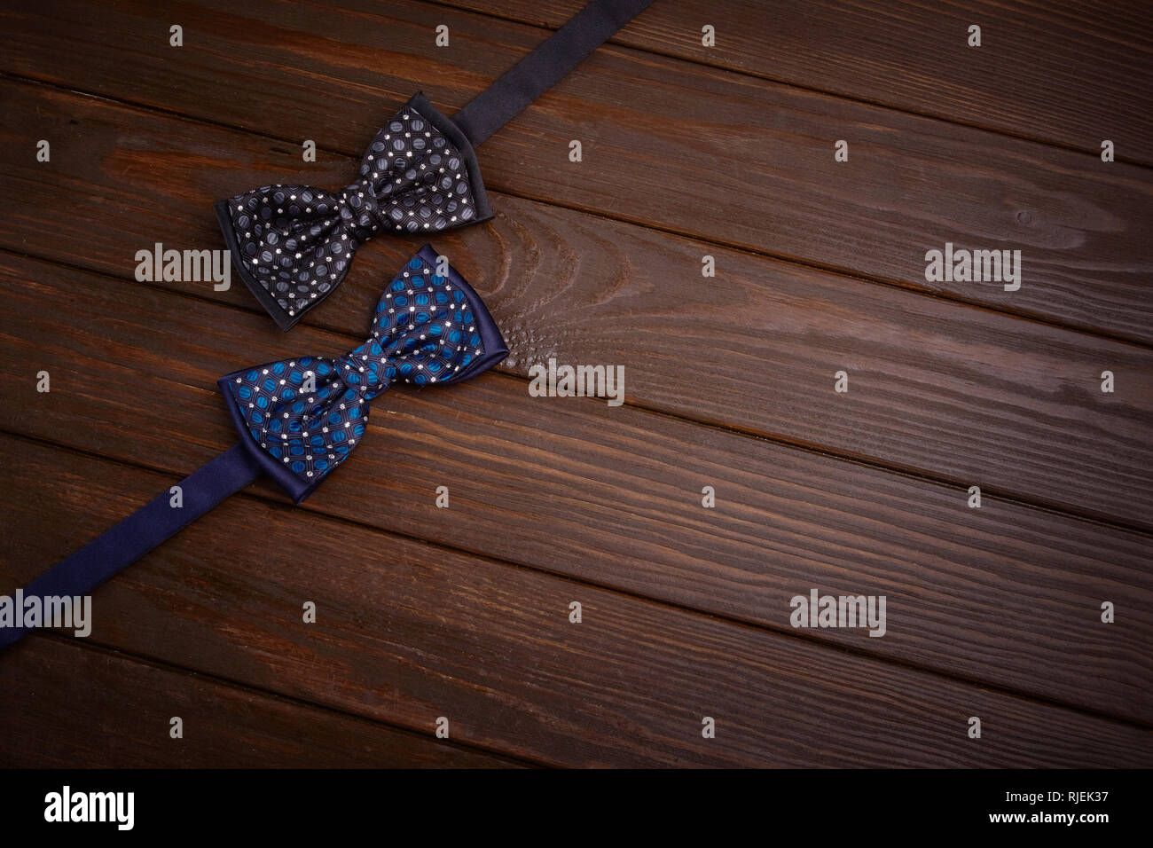 Two dark bowties with polka dots on a dark brown wooden board background. Invitation to  party place, special occasion, top view, space for text, copy Stock Photo