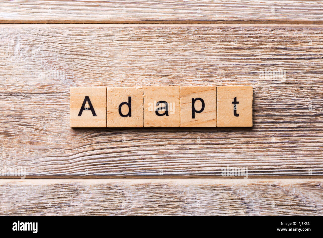 ADAPT word written on wood block. ADAPT text on wooden table for your desing, concept. - Stock Image