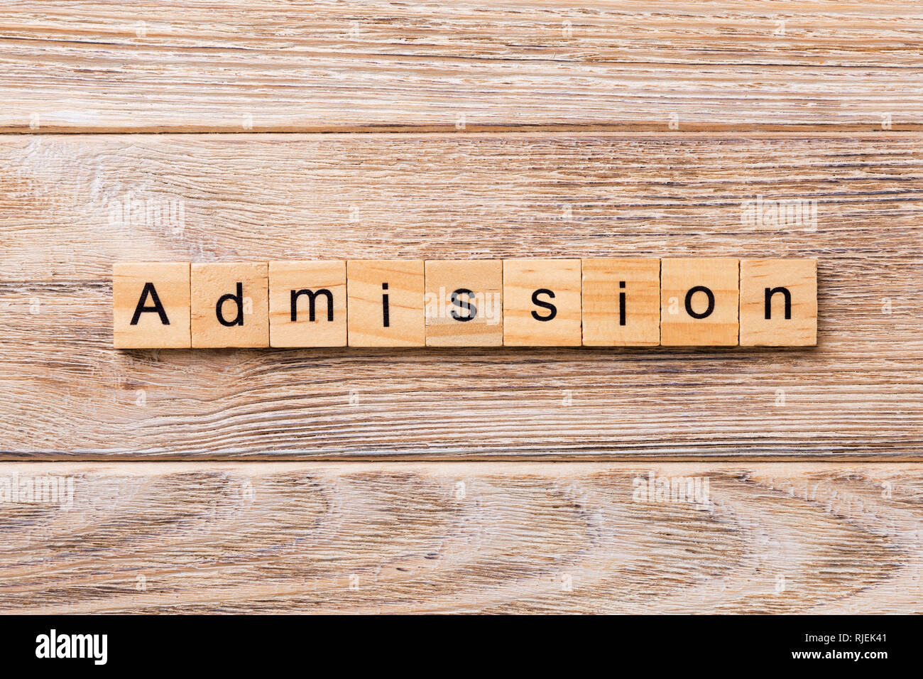 ADMISSION word written on wood block. ADMISSION text on wooden table for your desing, concept. - Stock Image
