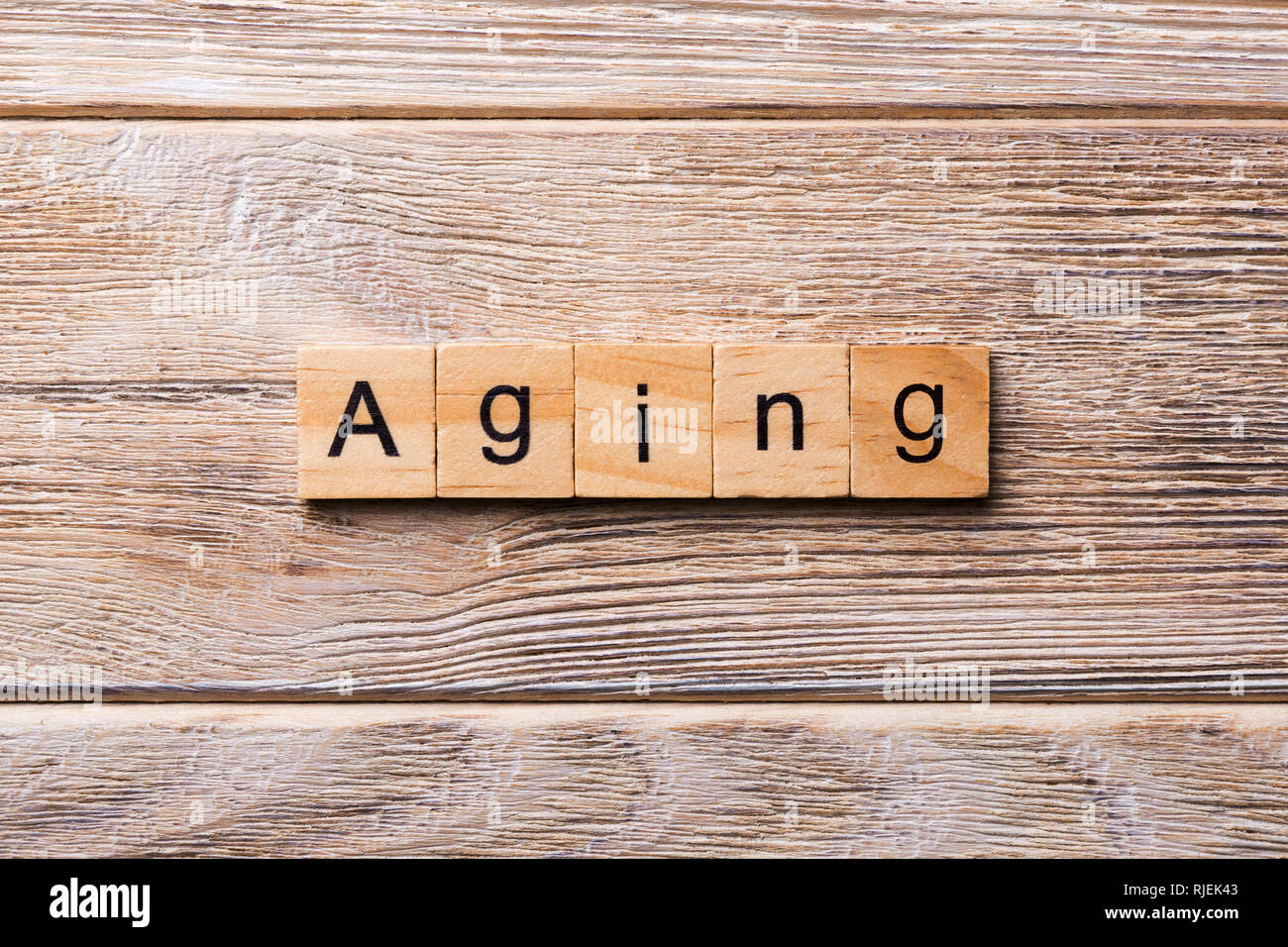 Aging word written on wood block. Aging text on wooden table for your desing, concept. - Stock Image
