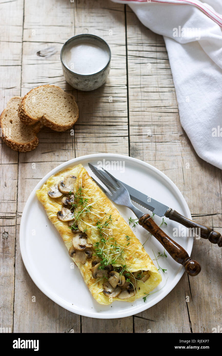 Vegetarian breakfast, omelette with mushrooms and cress, served with rye bread and coffee with milk. Rustic style. - Stock Image