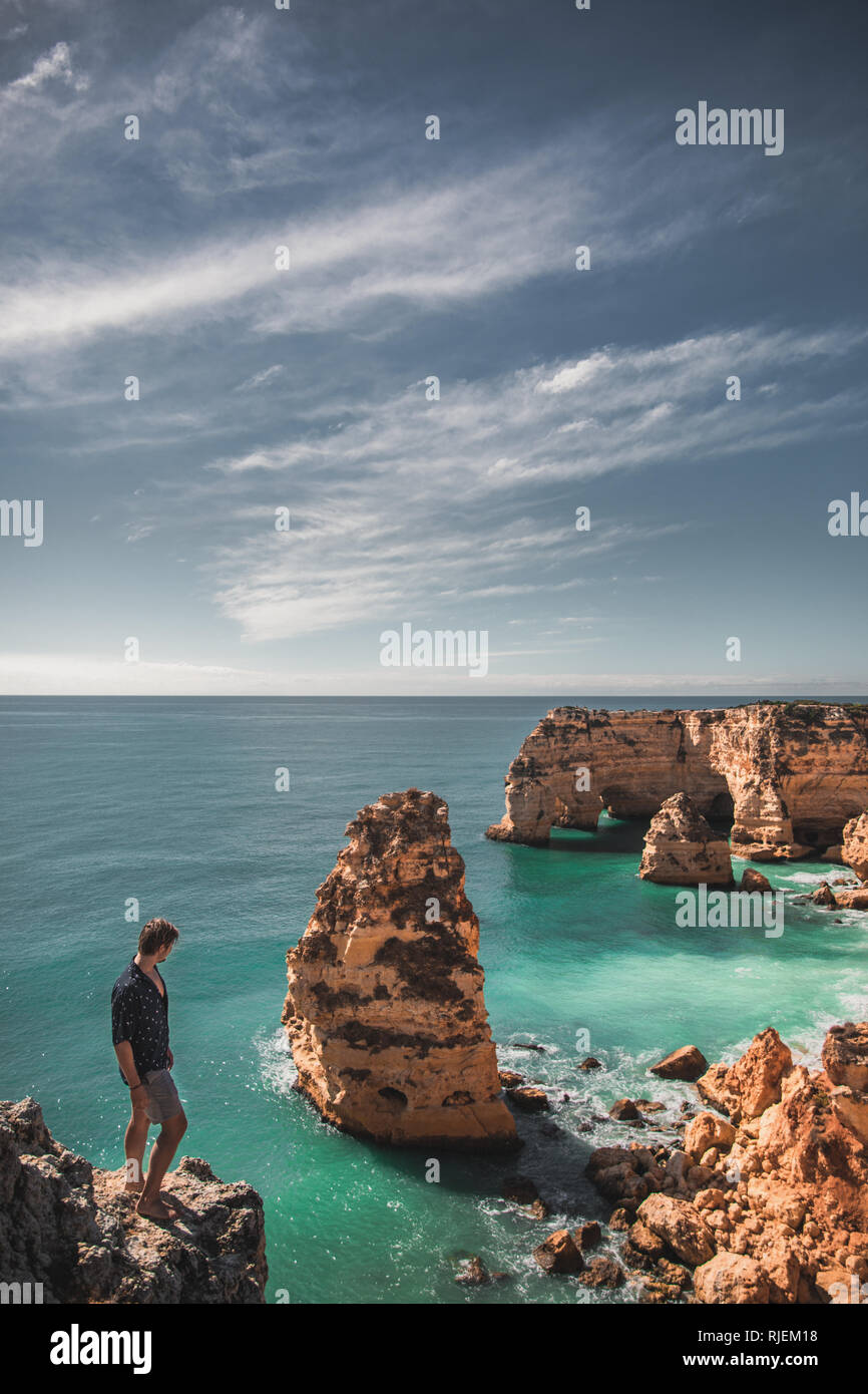 Man standing on the edge of a cliff at the beach with a panoramic view. - Stock Image
