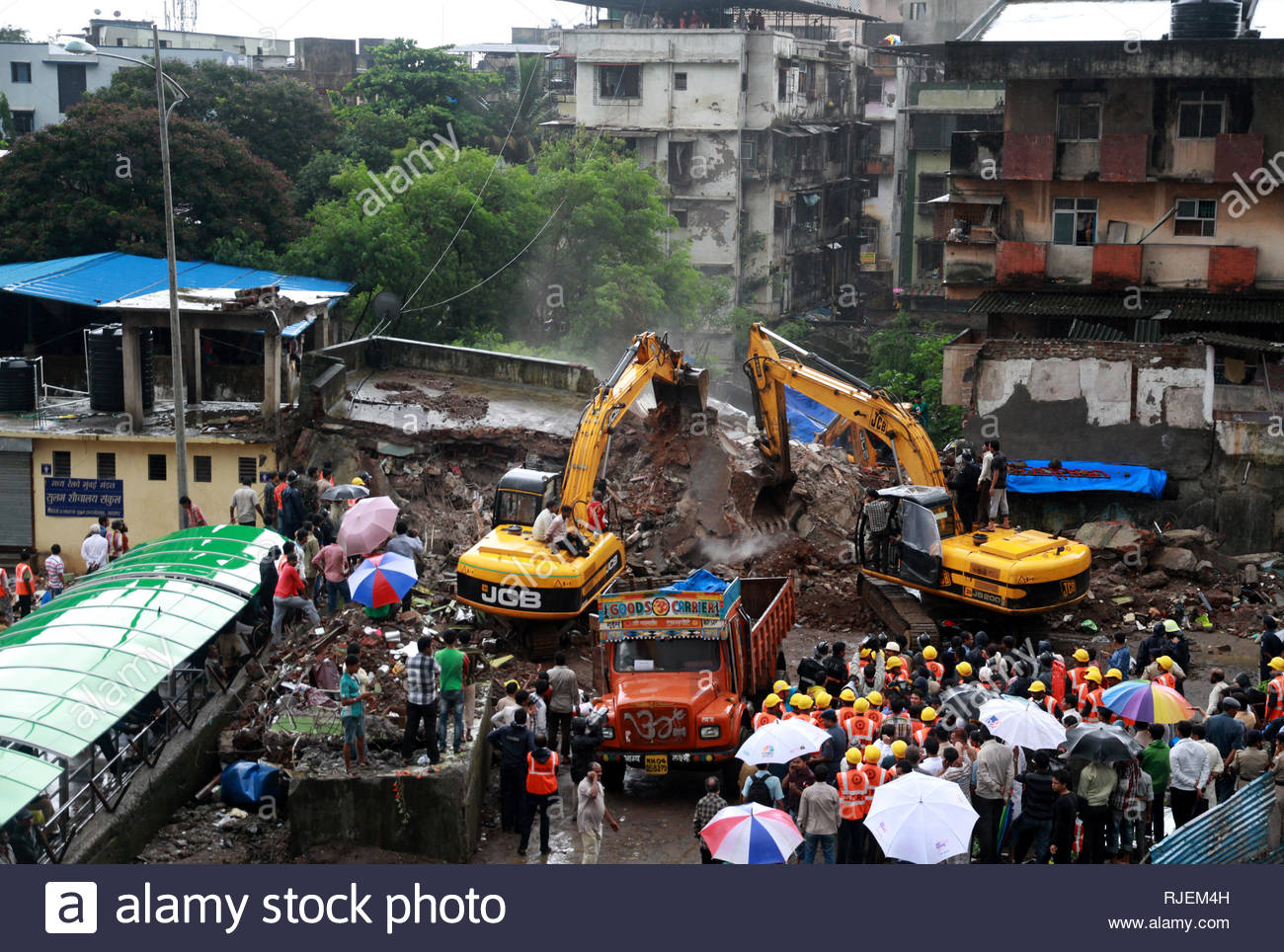 Earth movers pressed into service for rescue worker look for people trapped in the rubble of the building that collapsed at Mumbra, in Thane, Mumbai, India on June 21, 2013. The 35-year-old Shakuntala building, situated at Bazarpeth in Mumbra of Thane district collapsed after midnight. At least ten people are feared dead and several people are injured.(Ramesh Nair/ SOLARIS IMAGES) at least 14 injured. (Ramesh Nair/ SOLARIS IMAGES) - Stock Image
