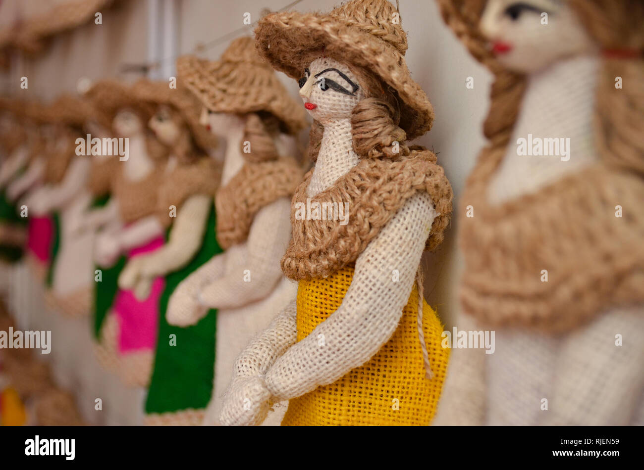 Jute puppet dolls wearing hat hanging on display for sale at a handicraft exhibition in Delhi Haat, Delhi, India Stock Photo