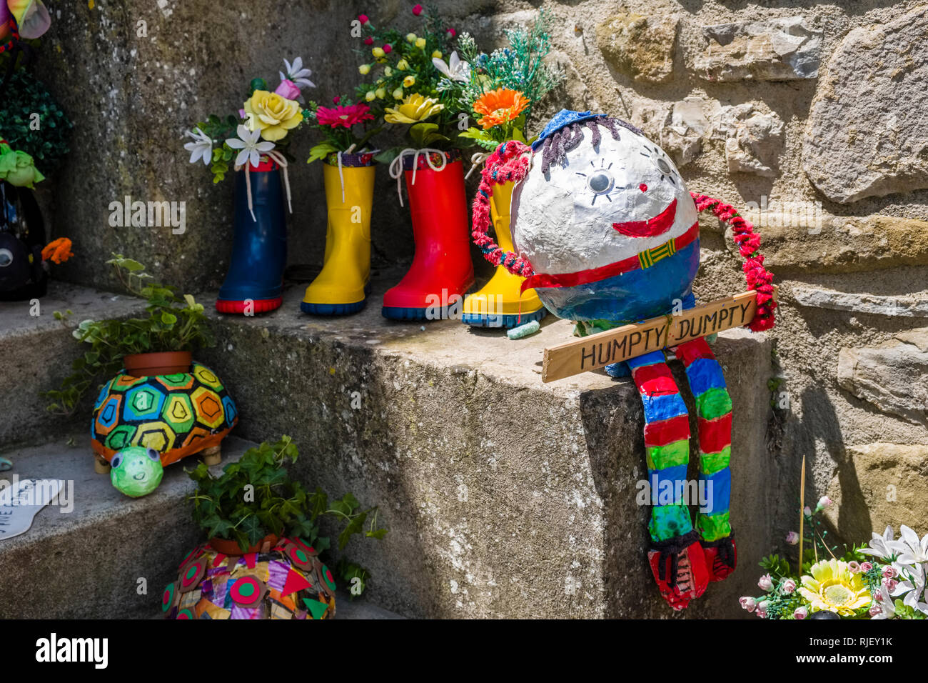 Colorful decoration with rubber shoes, flowers and a puppet at a house entrance - Stock Image