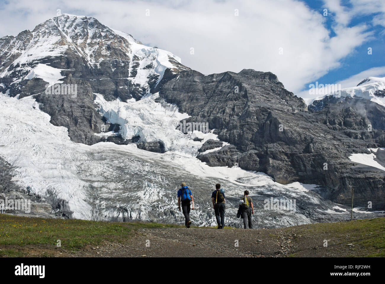 hikers under the nort face of the Mönch glacier, Bernese Alps, Switzerland Stock Photo