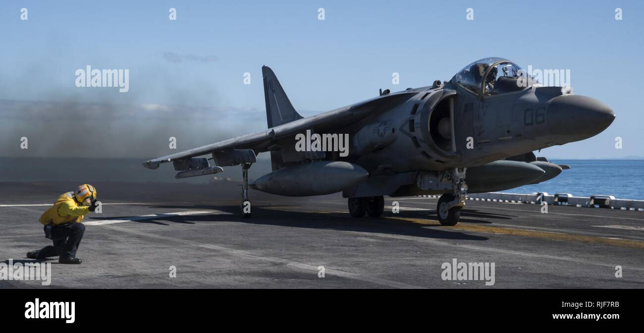 """CORAL SEA (Aug. 11, 2017) An AV-8B Harrier, assigned to the """"Tomcats"""" of Marine Attack Squadron (VMA) 311, takes off from the flight deck of the amphibious assault ship USS Bonhomme Richard (LHD 6) during a certification exercise (CERTEX). Bonhomme Richard, flagship of the Bonhomme Richard Expeditionary Strike Group, is supporting a certification exercise (CERTEX) for the 31st Marine Expeditionary Unit. During the CERTEX the 31st MEU will be evaluated on crisis response operations for a number of potential contingencies. CERTEX, taking place off the coast of and within Australia's Shoalwater B Stock Photo"""