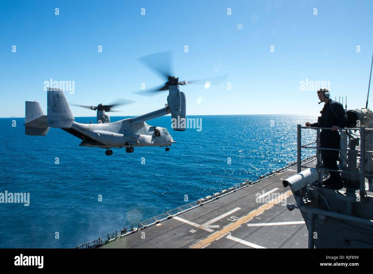 """CORAL SEA (July 20, 2017)  A Sailor observes an MV-22B Osprey assigned to the """"Dragons"""" of Marine Medium Tiltrotor Squadron (VMM) 265 (Reinforced) take off from the flight deck of the amphibious assault ship USS Bonhomme Richard (LHD 6) during Talisman Saber 17. Talisman Saber is a biennial U.S.-Australia bilateral exercise held off the coast of Australia meant to achieve interoperability and strengthen the U.S.-Australia alliance. Stock Photo"""