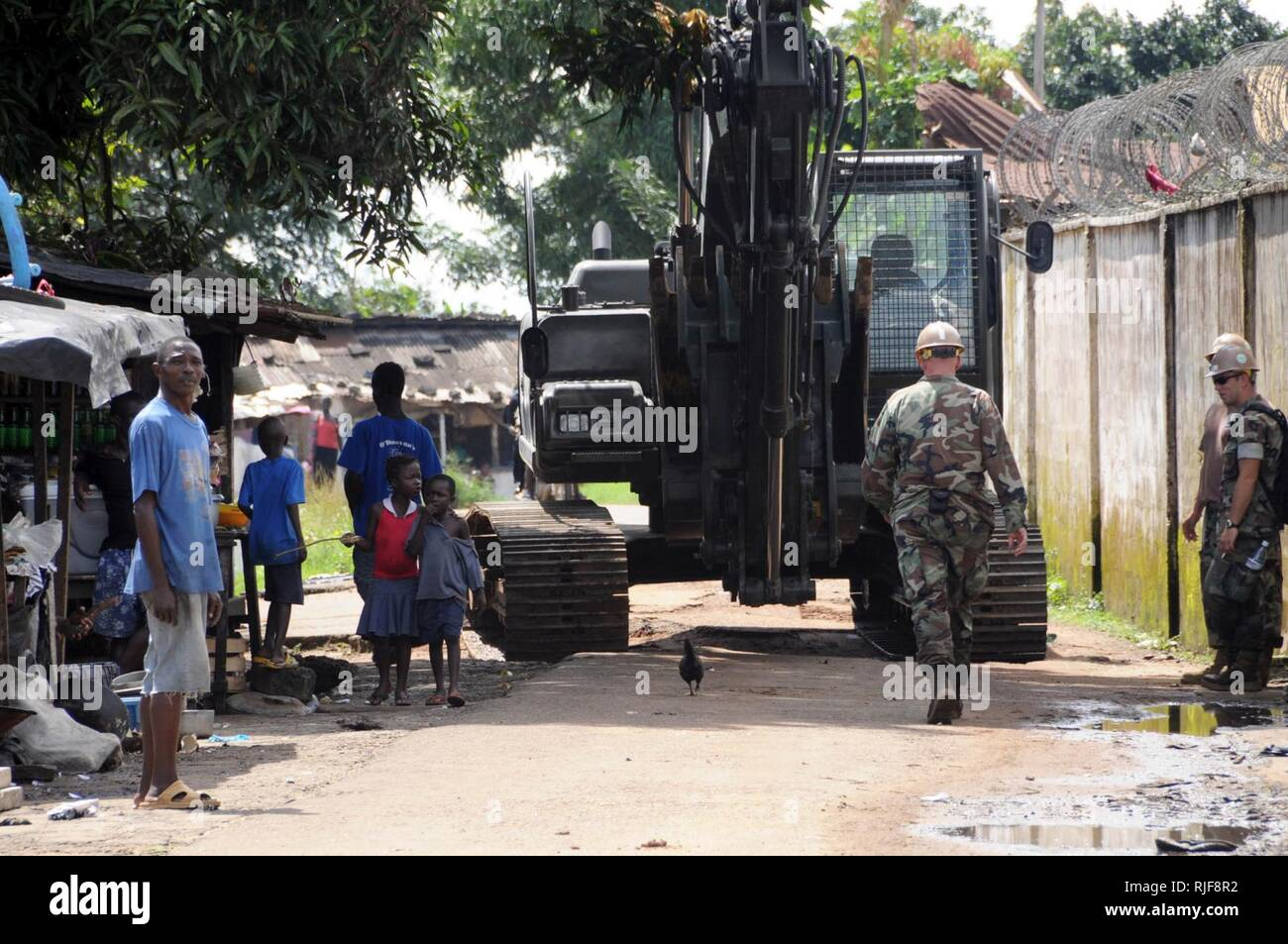 Personnel and equipment from Naval Mobile Construction Battalion 3, based out of Rota, Spain, makes its way through a local village after coming ashore in Monrovia, Liberia, Oct. 17.  The personnel and equipment were transported to the shore by amphibious landing craft attached to the Dutch Africa Partnership Station platform HNLMS Johan de Witt (L 801). The Seabees are in Liberia to rebuild the Liberian Coast Guard base that was destroyed  by factional groups in the country?s 2005 civil war.  Johan de Witt, a Royal Dutch Naval vessel, is the first European-led APS platform and is augmented by - Stock Image