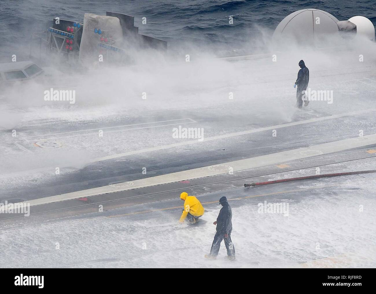 Sailors validate the shipboard firefighting system during an Aqueous Film Forming Foam system test on the flight deck aboard of the aircraft carrier USS George Washington to qualify the flight deck for operations. George Washington is conducting sea trials and carrier qualifications in the western Pacific Ocean following its first Selected Restricted Availability. Stock Photo
