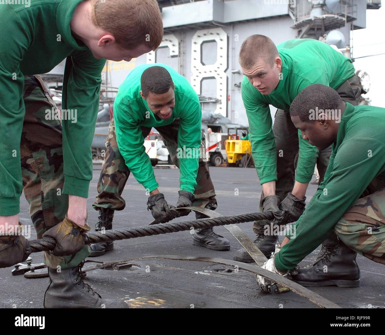 PACIFIC OCEAN (March 31, 2008) Sailors position a wire support under an arresting wire aboard the nuclear-powered aircraft carrier USS Nimitz (CVN 68). The wire support lifts the arresting wire off the deck enabling an aircraft tail hook to catch the wire during an arrested landing. Nimitz is deployed to the U.S. 7th Fleet operating in the western Pacific and Indian oceans. U.S. Navy - Stock Image