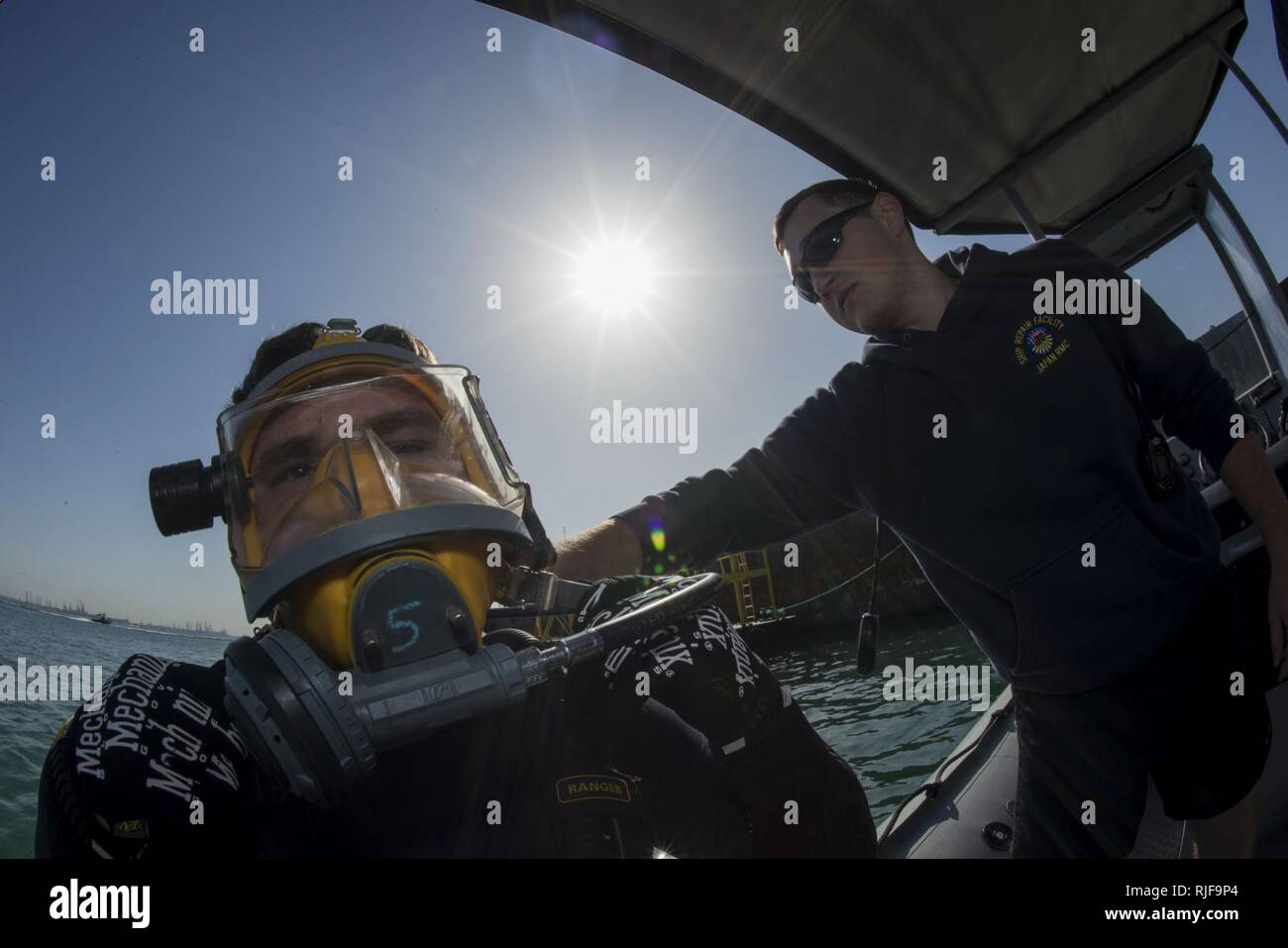 NAVAL SUPPORT ACTIVITY BAHRAIN (Jan. 6, 2016) Navy Diver 1st Class Scott Colvin conducts gear checks on Navy Diver 3rd Class Dakota Helm, assigned to Commander, Task Group (CTG) 56.1, prior to conducting an anti-terrorism force protection dive. CTG 56.1 conducts mine countermeasures, explosive ordnance disposal, salvage-diving and force protection operations throughout the U.S. 5th Fleet area of operations. - Stock Image