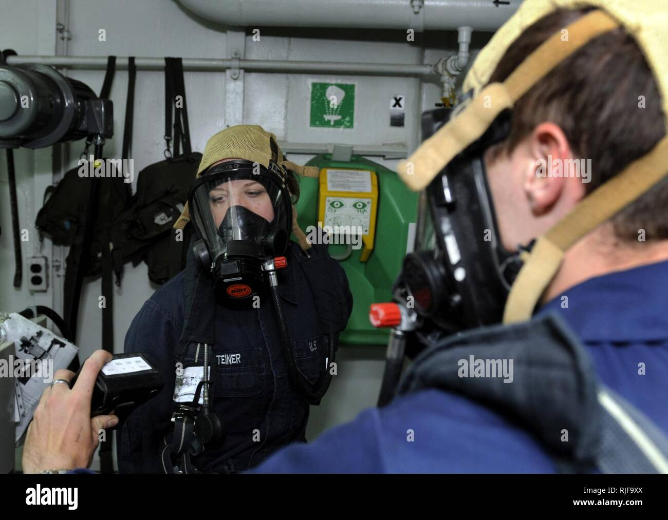 BUSAN, Republic of Korea (Aug. 25, 2009) Machinist's Mate Fireman Tara Steiner and Hull Maintenance Technician 2nd Class Christopher Leddy, flying squad rapid responders aboard the amphibious command ship USS Blue Ridge (LCC 19), take atmosphere readings during a toxic gas drill. - Stock Image