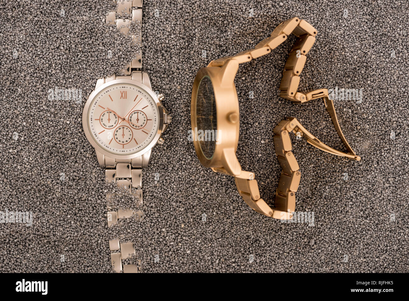 top view of wristwatches lying on golden sand - Stock Image