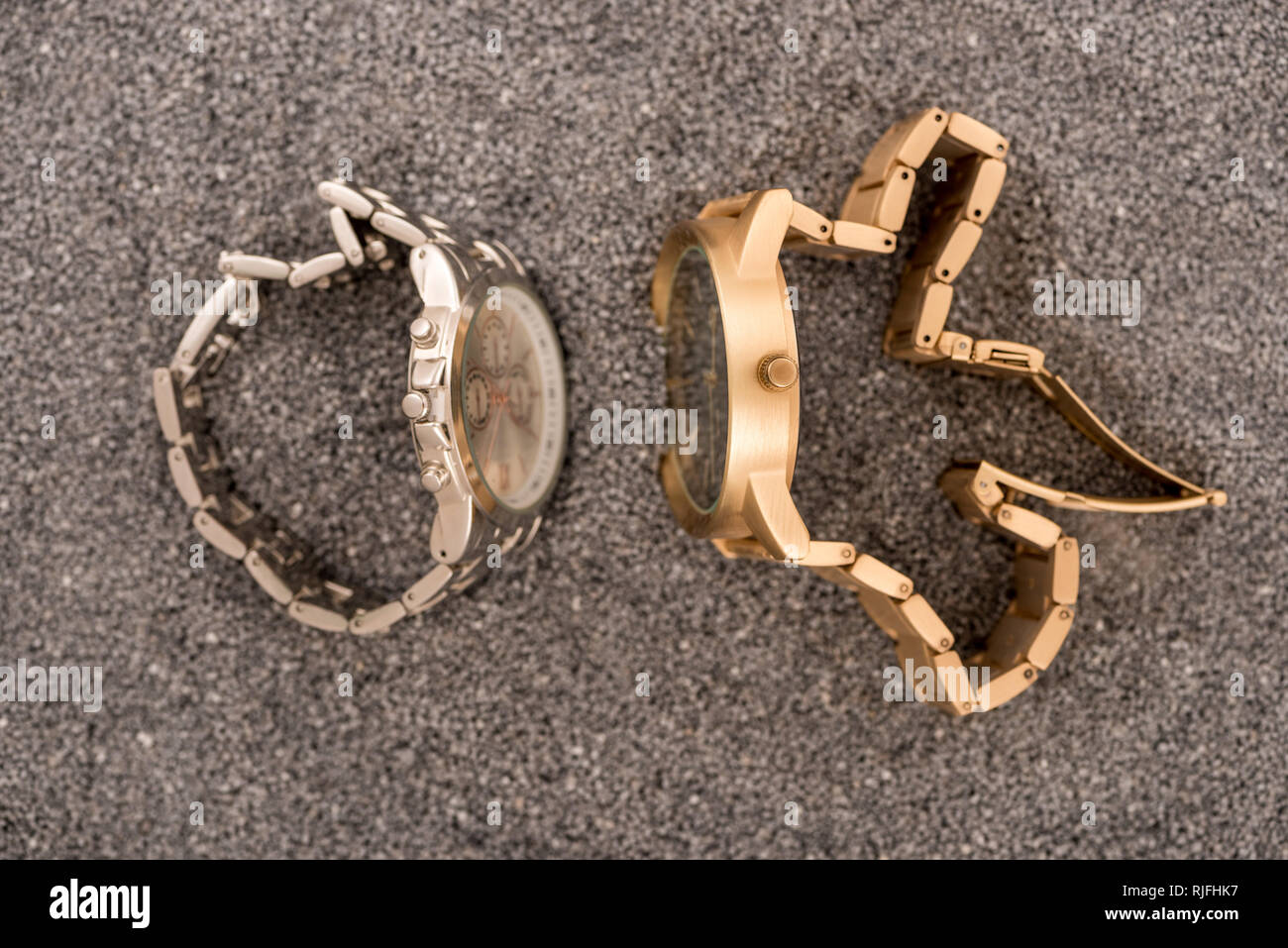 top view of wristwatches lying on sand - Stock Image