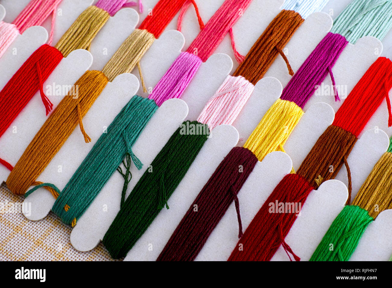 Colored embroidery threads on spools with canvas ready for cross stitch . Close-up. - Stock Image