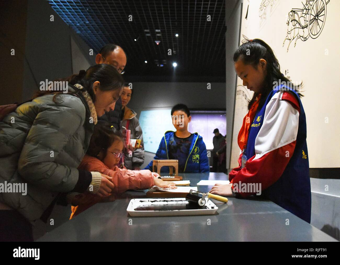 (190206) -- JINAN, Feb. 6, 2019 (Xinhua) -- A girl accompanied by her parents experiences the processes of movable-type printing at Shandong Museum in Jinan, east China's Shandong Province, Feb. 6, 2019. Shandong Museum witnessed lots of citizens and tourists on its first opening day during the Spring Festival. (Xinhua/Wang Kai) - Stock Image