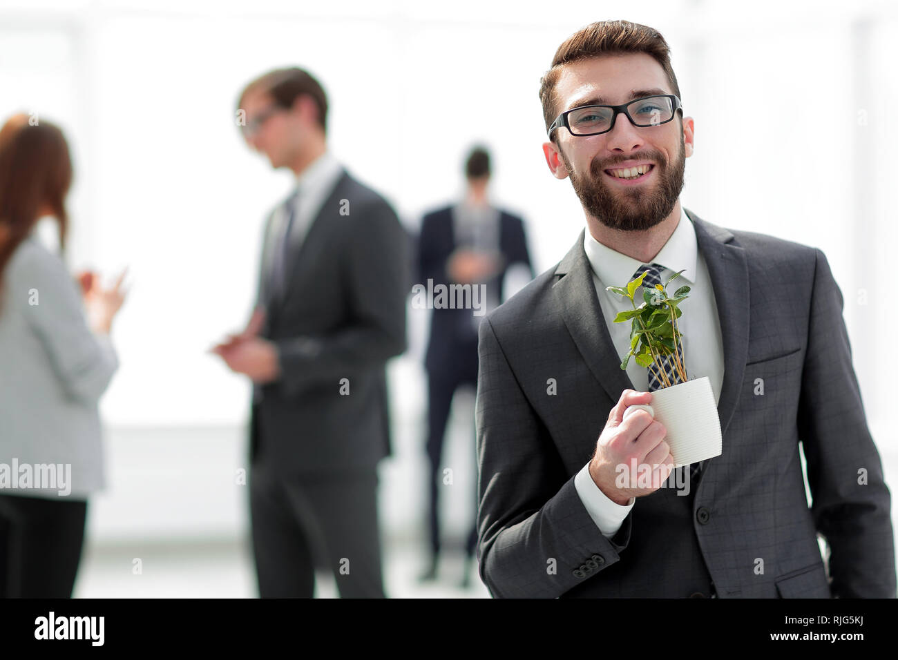 businessman with green young escape on blurred background - Stock Image