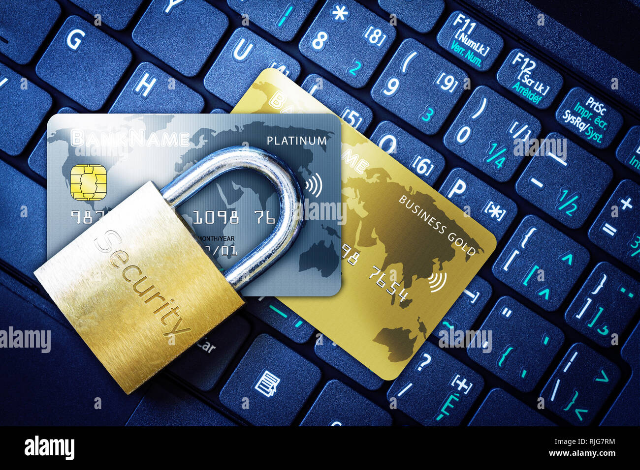 Golden padlock on top of fictitious credit cards on computer keyboard. Concept of Internet security, data privacy, cybercrime prevention for online sh - Stock Image
