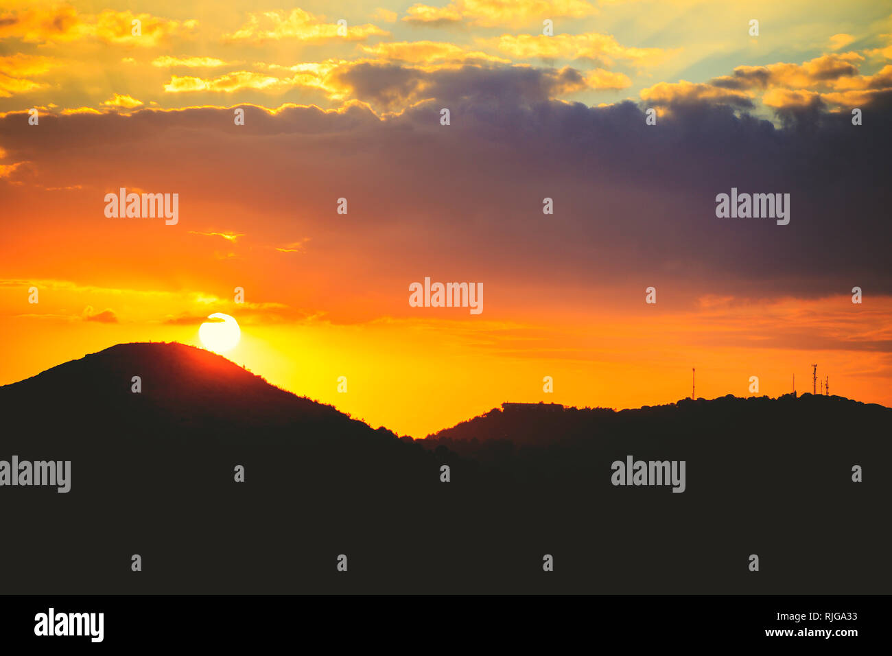 Panorama of sunset orange sky with sun shining above clouds. Mountain silhouette with reddish sky and sun - Stock Image