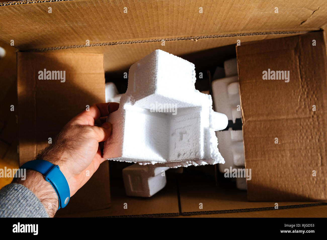 Man holding polystyrene packaging detail of a cardboard box during unboxing Stock Photo