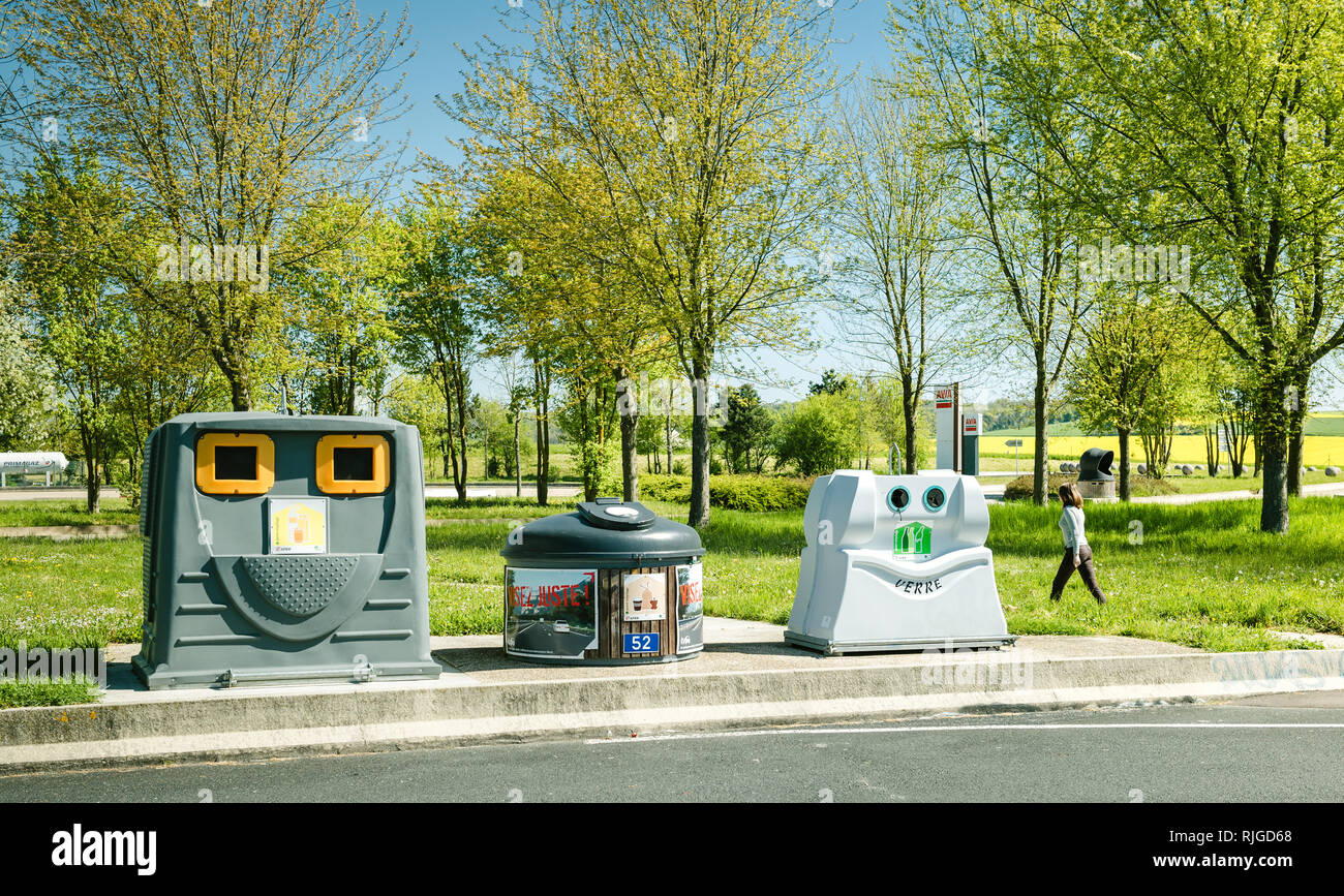 FRANCE - MAY 5, 2016: Three recycle waste bins for paper, food waste and glass on a parking AVIA area in France with firl waslking nearby - Stock Image