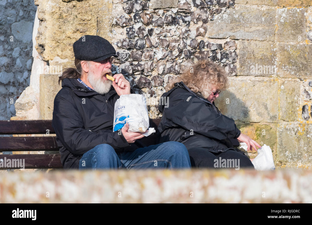 Senior couple sitting outside in Winter in the UK eating fish & chips from a paper bag. - Stock Image