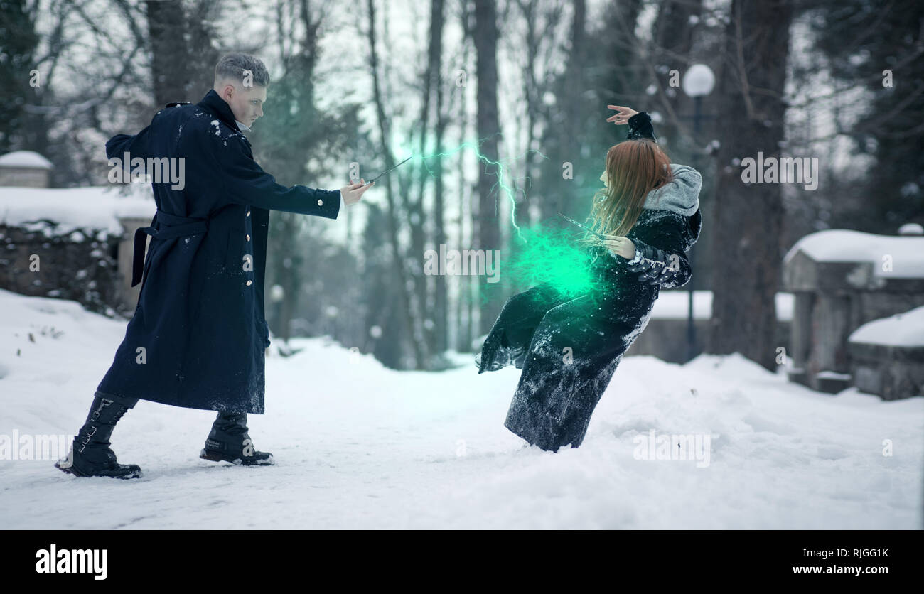 Battle of dark and light magicians with the help of magic wands and green beam on the snow background. Stock Photo