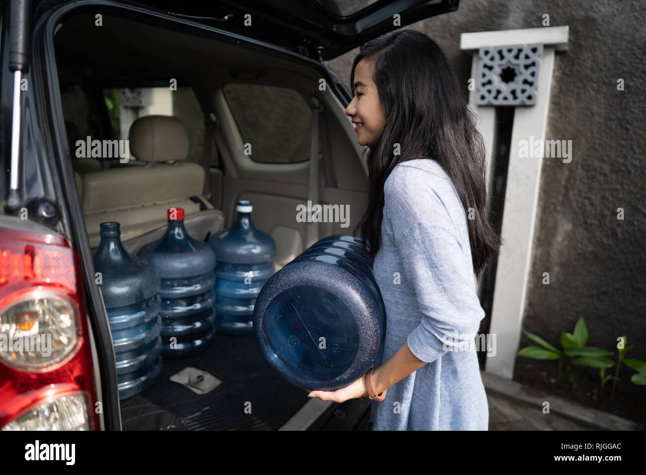 woman carrying a gallon of water put in car trunk - Stock Image
