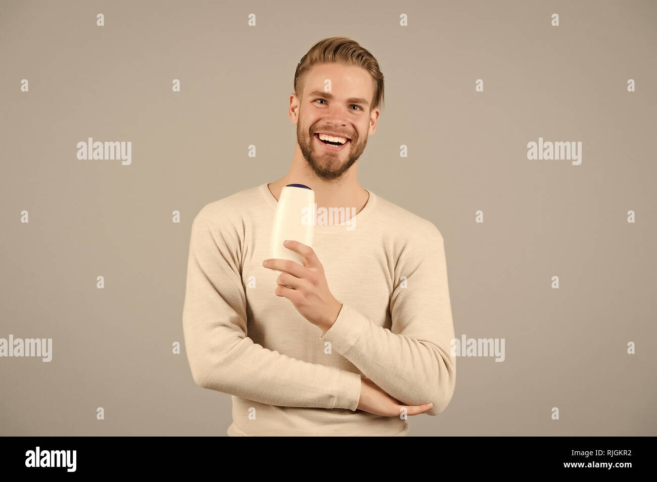 Hair care and beauty supplies concept. Man happy face holds shampoo bottle, grey background. Guy with bristle holds bottle shampoo, copy space. Man enjoy freshness after washing hair with shampoo. Stock Photo