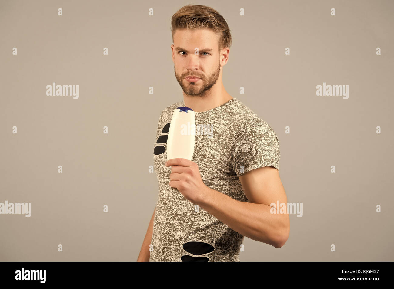 Man strict face holds shampoo bottle, grey background. Man enjoy freshness after washing hair with shampoo. Guy with hairstyle holds bottle shampoo, copy space. Hair care and beauty supplies concept. Stock Photo