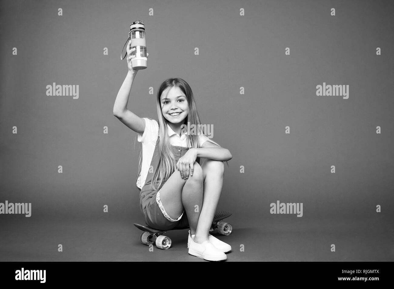 Staying hydrated. Girl happy face holds with water bottle while sit penny board violet background. Kid girl care body hydration. Active leisure and water balance. Active and healthy kid drink water. - Stock Image