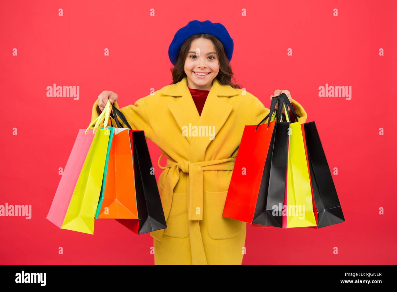 Fashionista enjoy shopping. Customer satisfaction. Prime time buy spring clothing. Obsessed with shopping. Girl cute kid hold shopping bags. Get discount shopping on birthday holiday. Nice purchase. - Stock Image