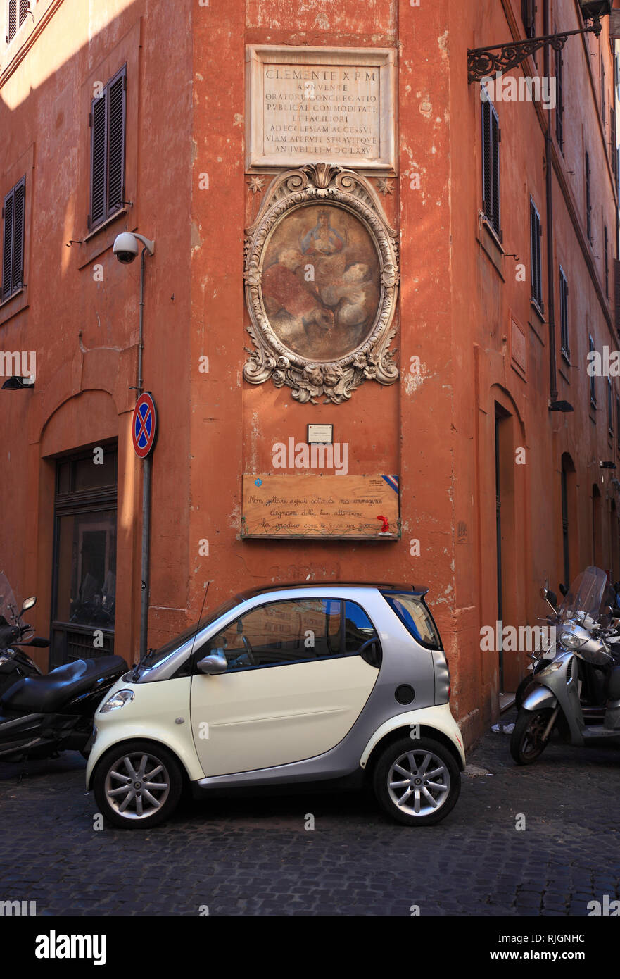 Religious image on a house wall, including a parked mercedes smart, at Campo de fiori, Rome, Italy - Stock Image