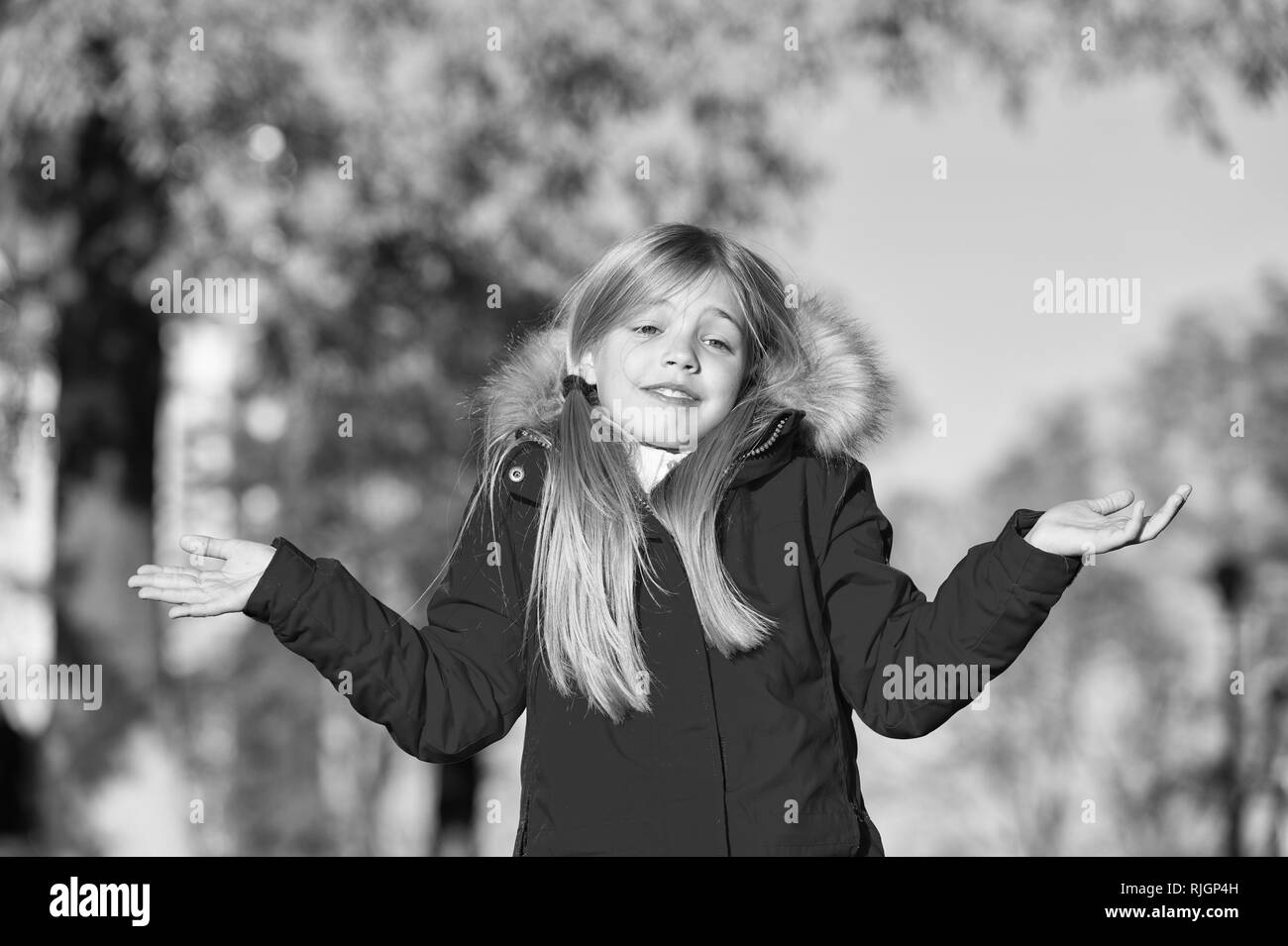 Happy small girl in autumn park. Small girl did it in mistake. Oops. Even the wisest of us can make a mistake. The first touches of autumn. Enjoy happy childhood. - Stock Image