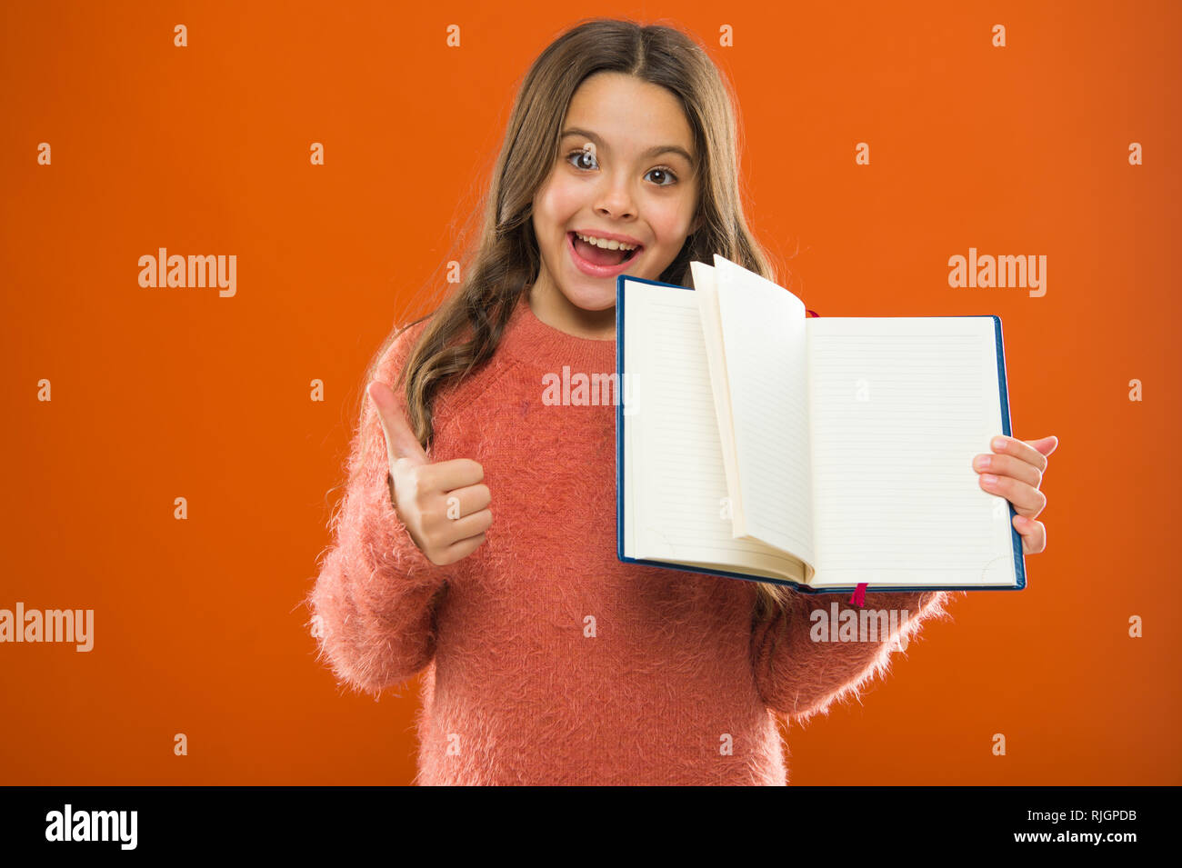 Starting to learn more. Girl hold book orange background. Child show open pages of book or notepad. Book store concept. Free books available to read. Childhood literature. Development and education. - Stock Image