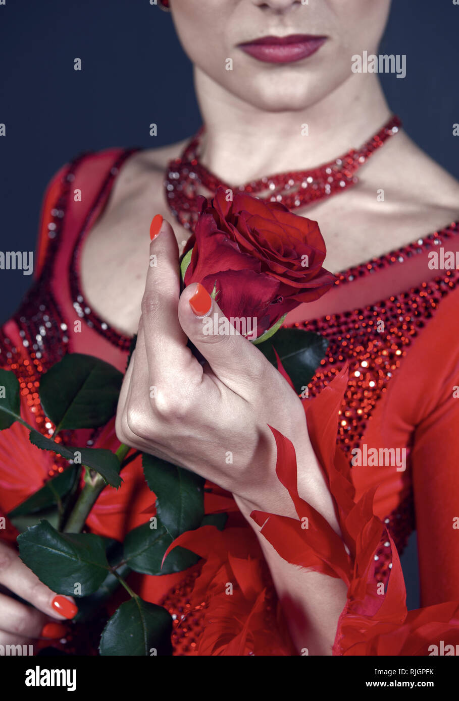 Rose flower in female hand on red dress. Love, desire, romance. Floristry, decor, design, floral shop. Womens day, 8 march spring Birthday anniversary holidays celebration - Stock Image