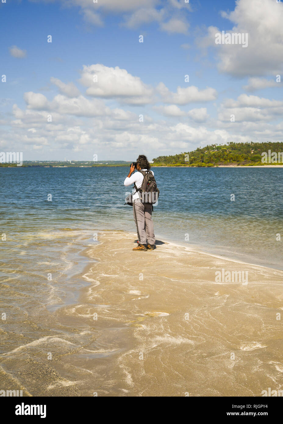 Male tourist taking pictures at the tip of Coroa do Aviao islet, Itamaraca island on the right - Pernambuco, Brazil - Stock Image