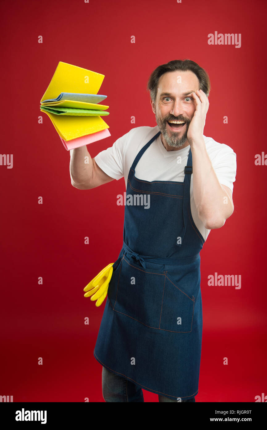 Cleaning service and household duty. Man in apron with gloves hold different sponges. Surface demand special care. Cleaning day today. Bearded guy cleaning home. On guard of cleanliness and order. - Stock Image