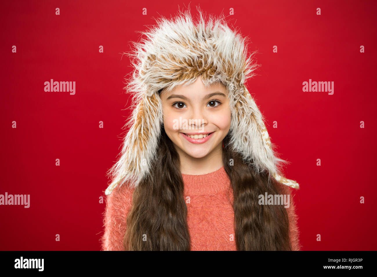Soft furry accessory. Tips for caring for fur garments. Child long hair soft hat enjoy softness. Winter fashion concept. Warm hat for cold weather. Kid girl wear hat with ear flaps red background. - Stock Image