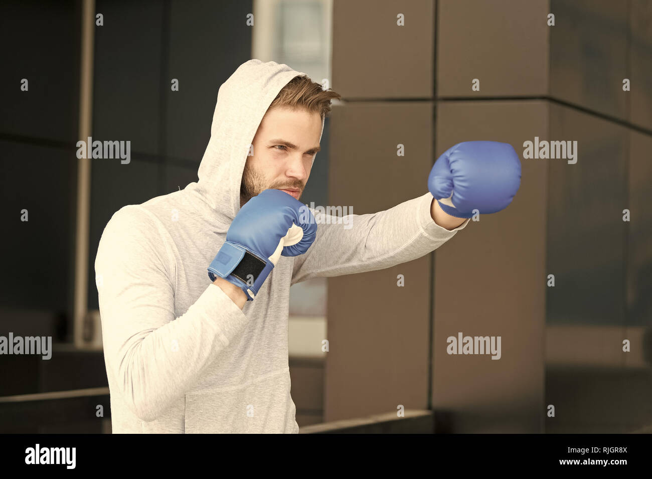 Man athlete on concentrated face with sport gloves practicing boxing punch, urban background. Training his boxing skills. Boxer hood head practices jab punch. Sportsman boxer training boxing gloves. - Stock Image