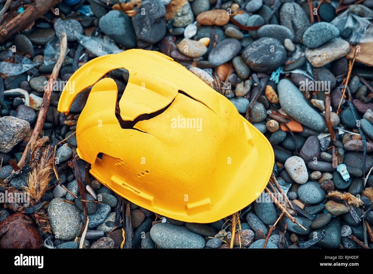 Cracked work helmet on the floor covered with pebble stones. Concept of work accident. - Stock Image