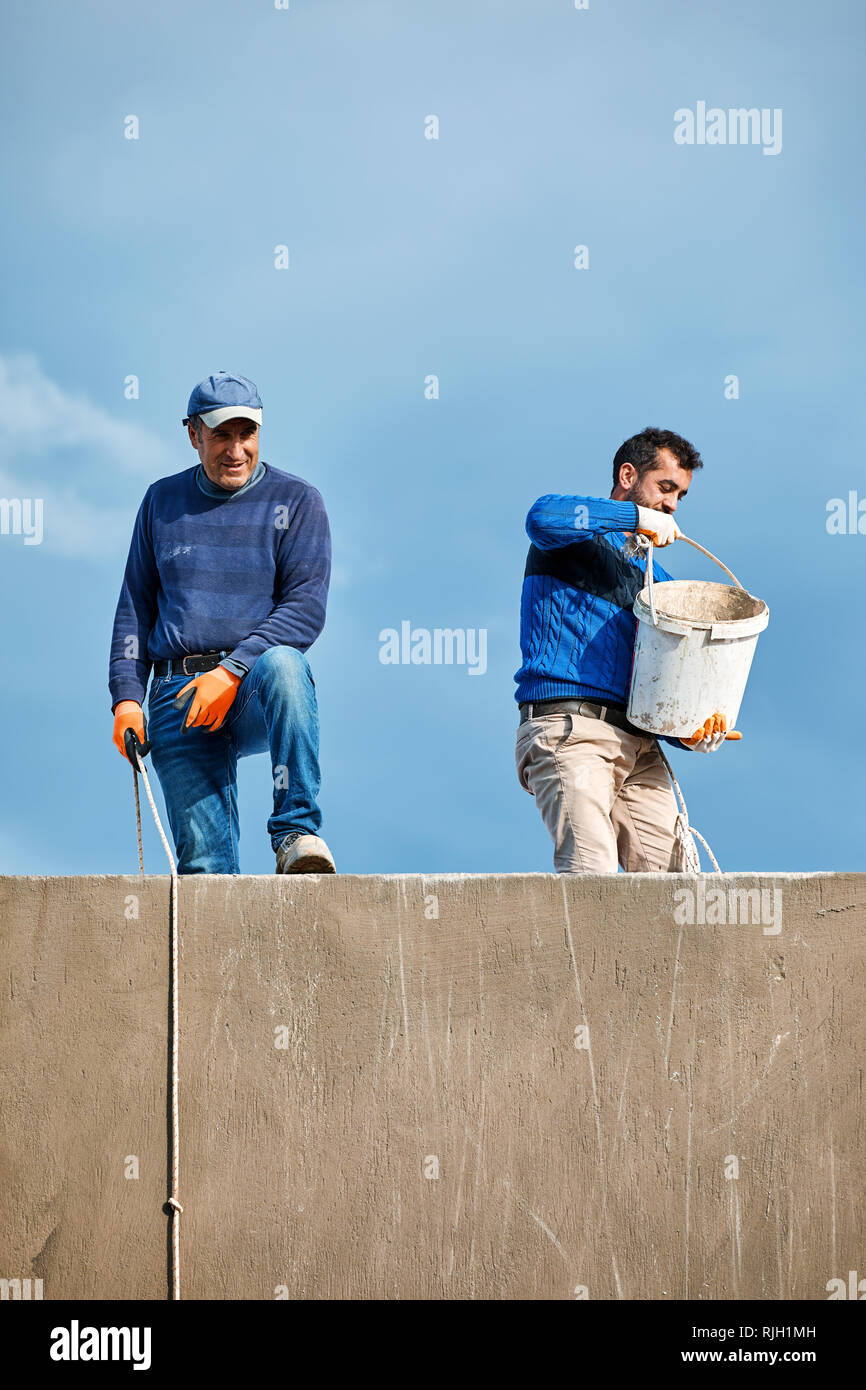 Bodrum, Turkey - January 2019: Two Turkish construction workers working at the top of a building and pulling the buckets up with ropes against a cloud - Stock Image