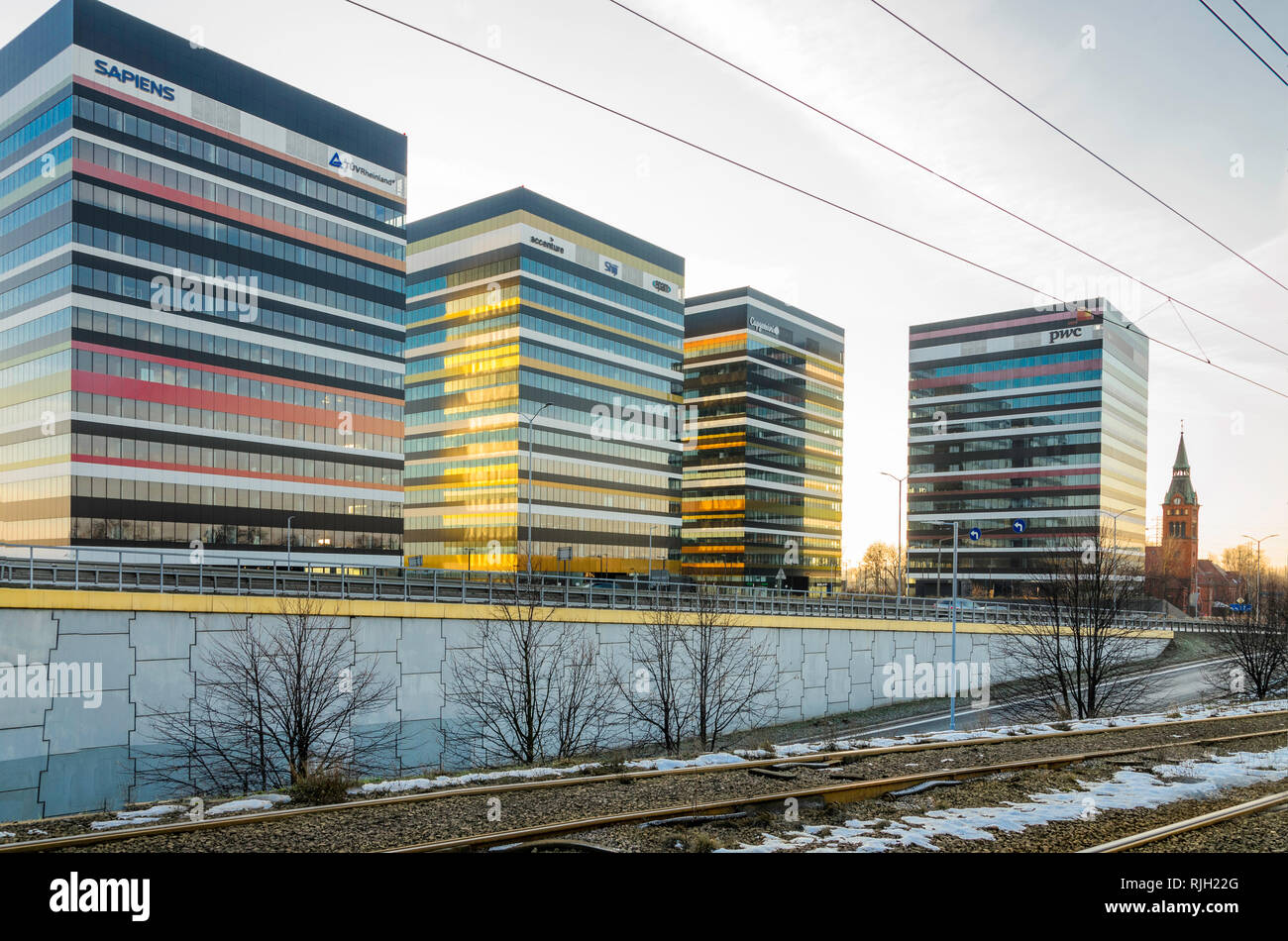 Katowice, Silesia, Poland: January 19, 2019: Tiramisu business center buildings in Katowice, Poland with a nearby tram line and a neogothic church - Stock Image