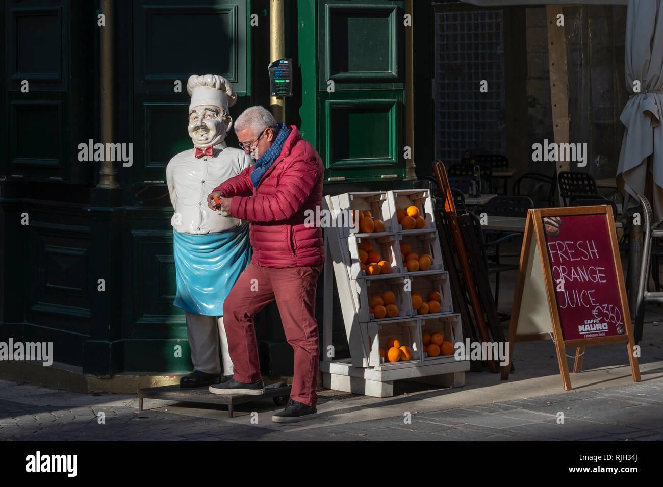 Orange seller standing outside a cafe bar in Valletta, Malta. - Stock Image
