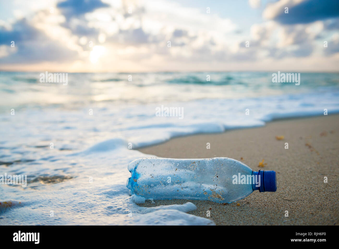 Used plastic water bottle washed up on the shore of a tropical beach, highlighting the worldwide crisis of plastic pollution on even remote islands Stock Photo