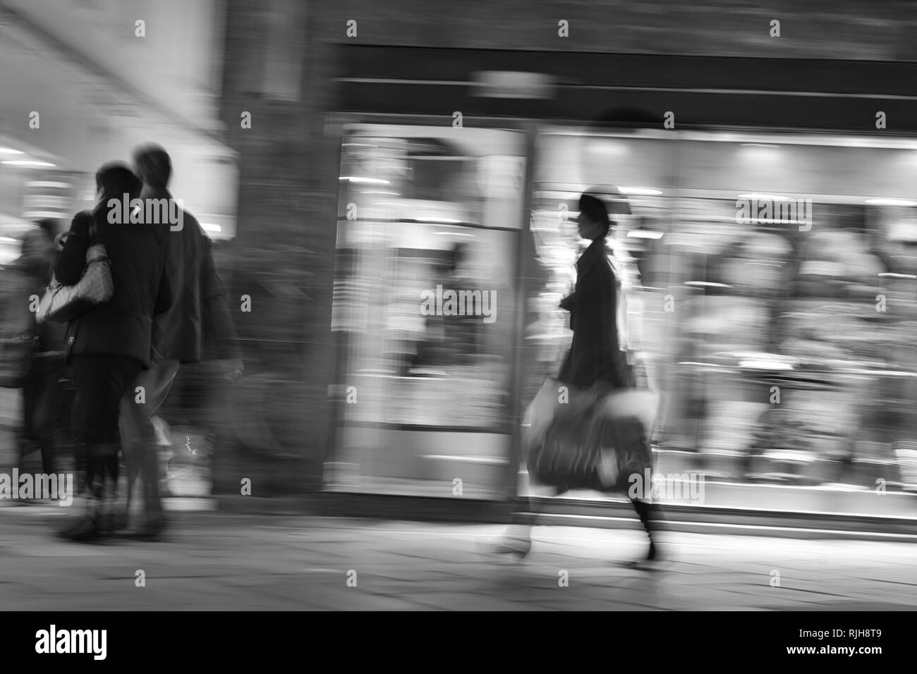 Shopping in Venice at night time, illuminated shops, blurred photograph, black and white, Venetia, Italy, Southern Europe - Stock Image