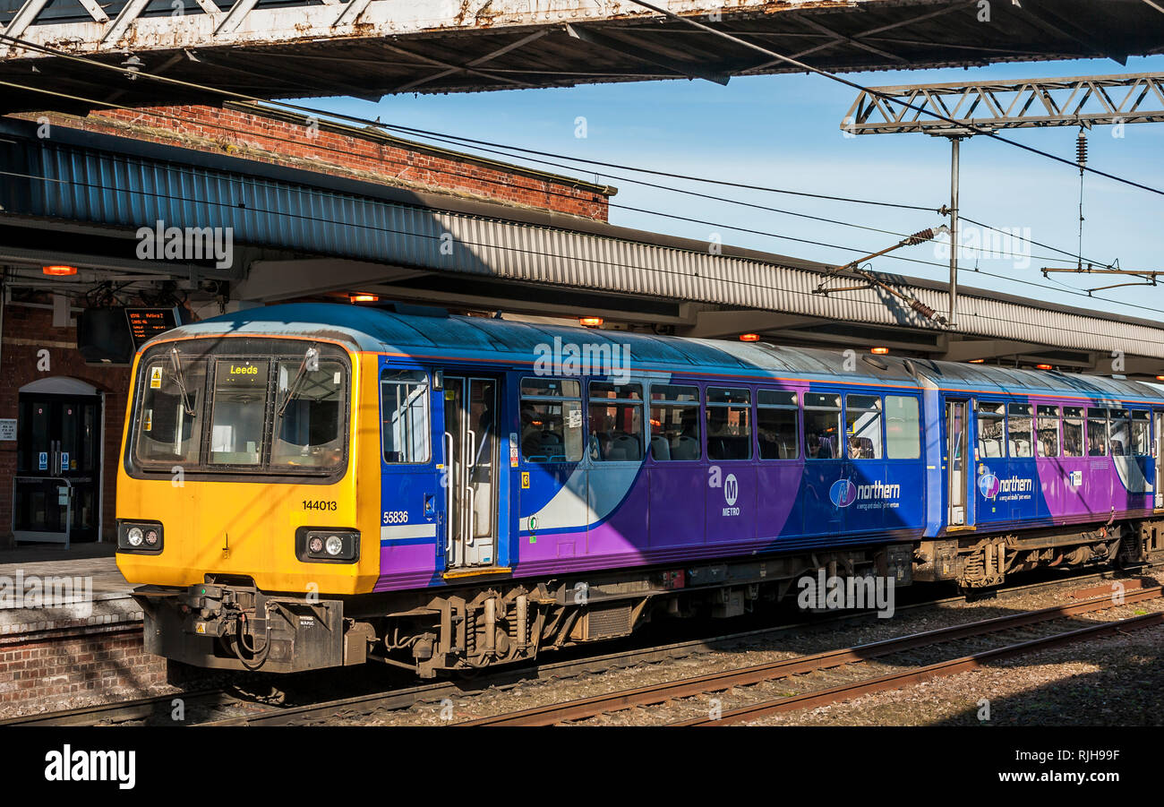 Class 144 Pacer diesel multiple unit train in Northern livery waiting at a station, on it's way to Leeds, UK. - Stock Image
